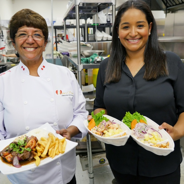 Carmen displaying a plate of Lomo Saltado and Maria displaying two plates of our delicious Ceviche.